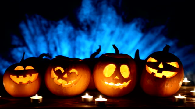 Halloween pumpkins on smoky background Halloween pumpkins over blue light rays and smoke at background with copy space for text above, front view, locked down video decoration stock videos & royalty-free footage