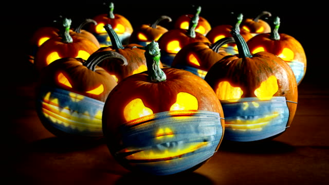 Halloween pumpkins Halloween pumpkins in a protective medical face masks.  Second wave of coronavirus infection in autumn. New normal concept. Jack o lantern and Covid-19 concept. halloween covid stock videos & royalty-free footage