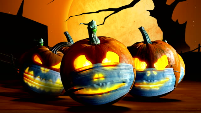 Halloween pumpkins Halloween pumpkins in a protective medical face masks on  cemetery background. Second wave of coronavirus infection in autumn. New normal concept. Jack o lantern and Covid-19 concept. halloween covid stock videos & royalty-free footage