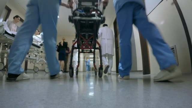 POV Hallway of a hospital department Point of view low angle shot of a hallway in a hospital. Two nurses pushing a stretcher down hall, a woman is talking to man lying on the stretcher and two people talking to a doctor. hospital gurney stock videos & royalty-free footage