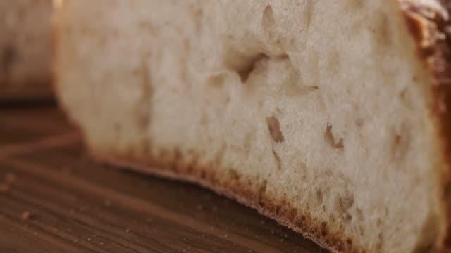 halvorna av färska ciabatta på oliv skärbräda - brödlimpa bildbanksvideor och videomaterial från bakom kulisserna