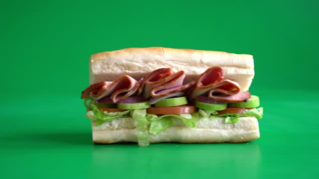 Ham and salad submarine sandwich Ham and salad submarine sandwich studio workplace stock videos & royalty-free footage