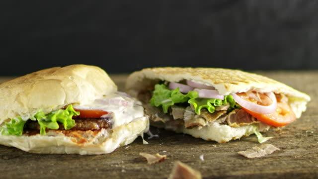 slo-mo-ds-hamburger und döner fallen auf einem tisch - döner stock-videos und b-roll-filmmaterial