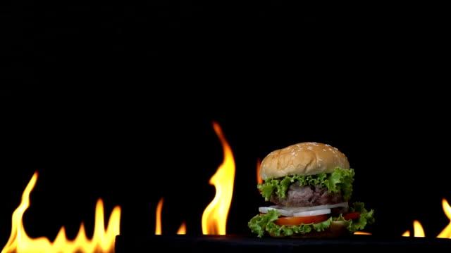 hamburger fast food on fire slow motion background. - cheeseburger filmów i materiałów b-roll