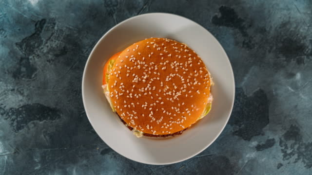 Hamburger on plate, top view. Delicious burger eating animation, stop motion. Fast food concept video