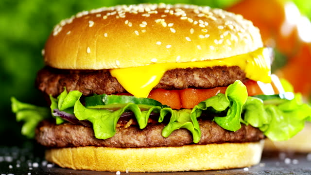 a hamburger with onions, tomatoes and parmesan salad and sauces that give flavor served with or without fries. the hamburger is a typical american food, a food to fast food. - cheeseburger filmów i materiałów b-roll