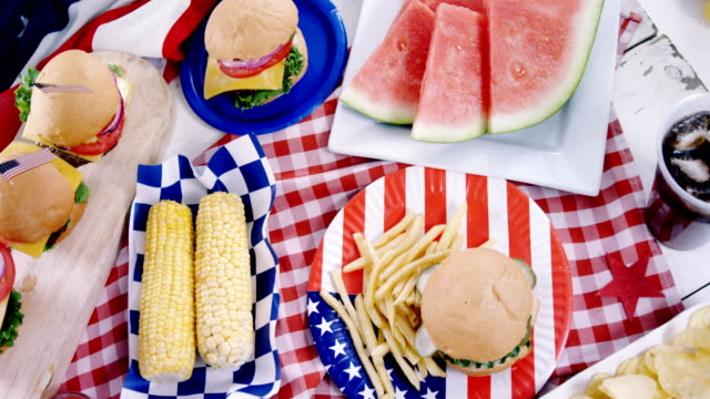 Hamburgers and french fries served on table with 4th july theme video