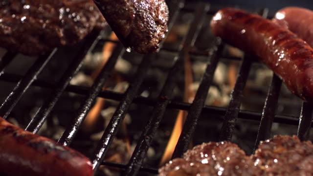 hamburgery i kiełbasa na grill - szpatułka przybór do gotowania filmów i materiałów b-roll