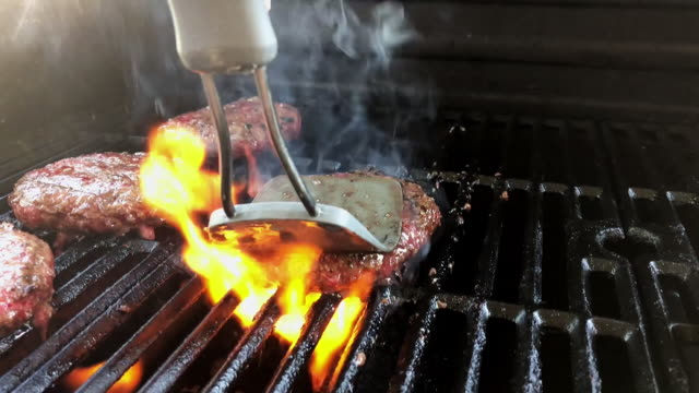 Hamburgers Cooking On the Grill The grill master forces the juices out of the hamburger to get the grill to flame up and cook the patty faster. ground beef stock videos & royalty-free footage