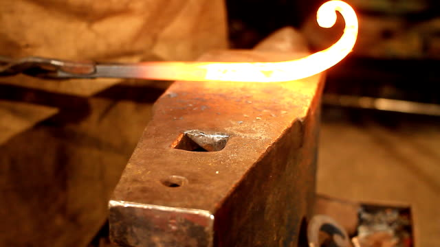 Hammer and anvil Blacksmith working on a piece of glowing hot iron anvil stock videos & royalty-free footage