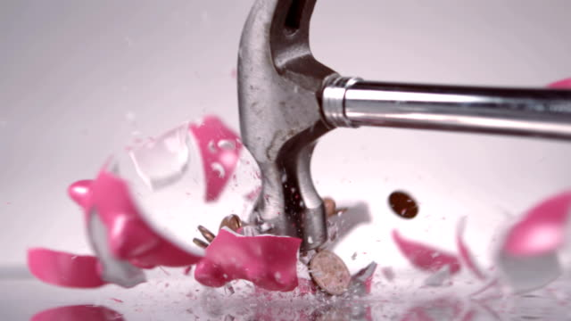 Hammer breaking a piggy bank Hammer breaking a piggy bank against white background piggy bank stock videos & royalty-free footage
