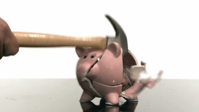 Hammer smashes a piggy bank, slow motion video