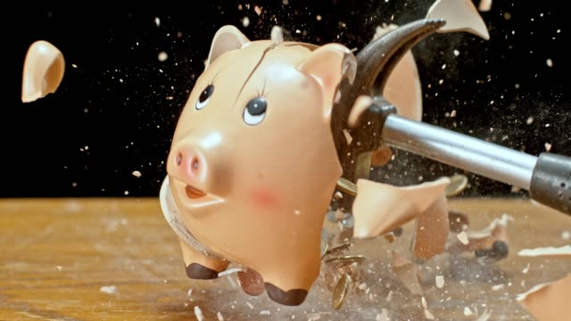 SLO MO LD Hammer smashing a piggy bank and coins flying into the air Slow motion medium locked down shot of a hammer striking a piggy bank on the desk and the coins fly into the air. Shot in Slovenia. piggy bank stock videos & royalty-free footage
