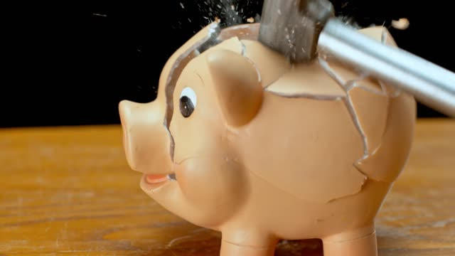 SLO MO LD Hammer smashing a piggy bank Slow motion medium locked down shot of a hammer striking a piggy bank on the desk and smashing it into pieces. Shot in Slovenia. piggy bank stock videos & royalty-free footage