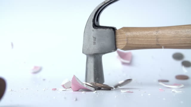 Hammer Smashing Piggy Bank In Slow Motion Slow motion sequence of hammer smashing pink ceramic piggy bank.Shot on Sony FS700 at frame rate of 50fps piggy bank stock videos & royalty-free footage