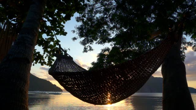 Hammock at sunset on the beach. Slow motion video