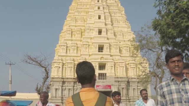 hampi, karnataka, indien - circa 2017 pilgrimer kommer och går från enorma, uråldriga dicks templet. - india statue bildbanksvideor och videomaterial från bakom kulisserna