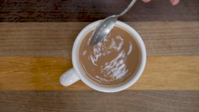 Hand adding a teaspoon of sugar to a cup of tea or coffee with milk