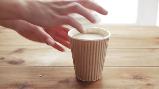 hand adding and stirring sugar in cup of coffee - coperchio video stock e b–roll