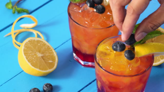 Hand adding blueberries toppings on the glass of orange juice cocktail drink