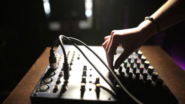 Hand adjusting button on sound mixer video