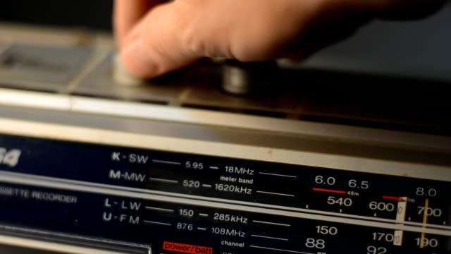 Hand adjusts radio channels recorder. video