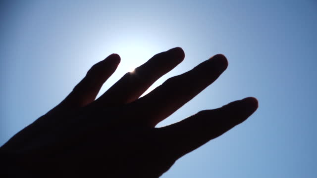 Hand against sun Hand against sun covering stock videos & royalty-free footage