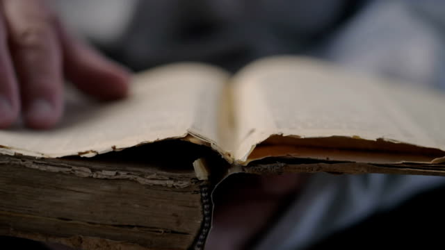 hand and old book. a man's hand holds a book and read. - религиозные тексты стоковые видео и кадры b-roll