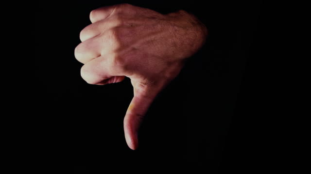 Hand appearing with a negative and large thumbs down signal video