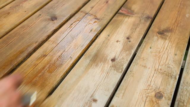 hand auftragen deck-färbung mit großen pinsel - schmutzfleck stock-videos und b-roll-filmmaterial