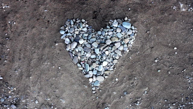 Hand arranges small stones in the heart