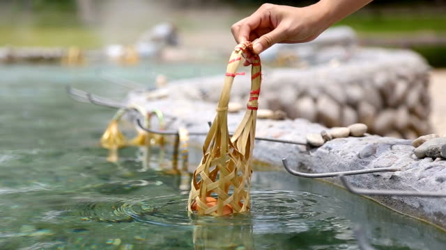 Hand boiling eggs in bamboo basket at hot spring. Full HD Hand boiling eggs in hot spring. San Kamphaeng in Chiang Mai, Thailand. boiled stock videos & royalty-free footage