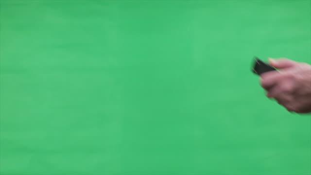 Hand Brandishing Switch Blade Knife Over Green Screen video