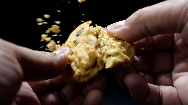vídeos y material grabado en eventos de stock de la mano rompe una galleta de chocolate a cámara lenta - galleta dulces