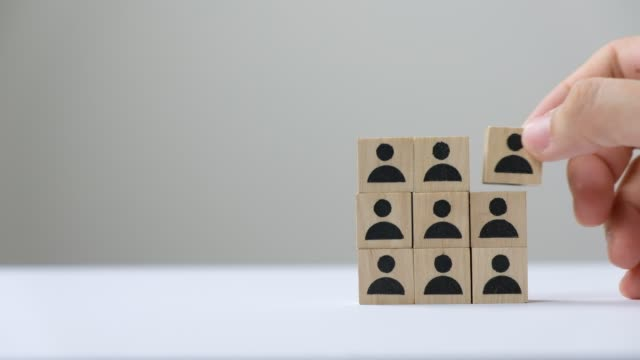 Hand building a team by putting wood cube block people icon