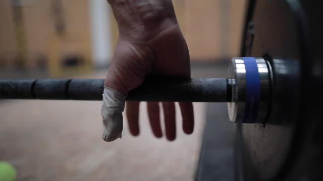 hand fängt gewicht im fitness-studio - gewichtstraining stock-videos und b-roll-filmmaterial