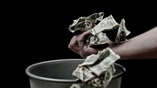 SLO MO Hand catching crumpled dollar bills