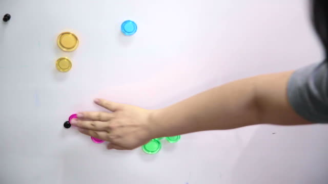 Hand categorise colourful magnet on magnetic board video