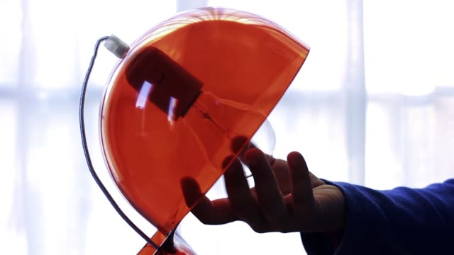 Hand Changing A Light Bulb Of A Red Lamp.