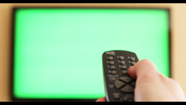 Hand Changing Channels on Green Screen TV A 4K video clip of a woman's hands changing the channels on a television with a green screen. changing channels stock videos & royalty-free footage