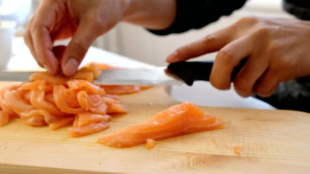 hand chef using knife slice raw salmon on chopping board - sashimi video stock e b–roll
