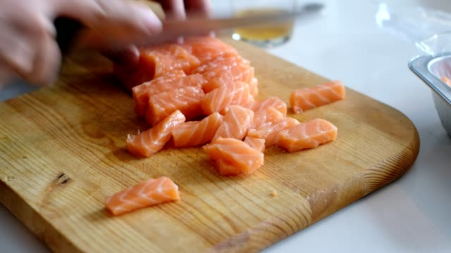 Hand chef using knife slice raw salmon on wooden chopping board video