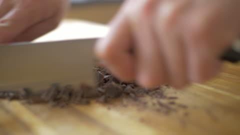 vídeos y material grabado en eventos de stock de bloque de chocolate de corte a mano en tabla de cortar madera - chocolate
