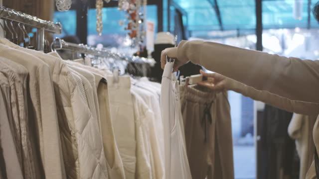 ショッピングモールの衣料品小売店で女性の手を閉じてドレスを選ぶ ビデオ