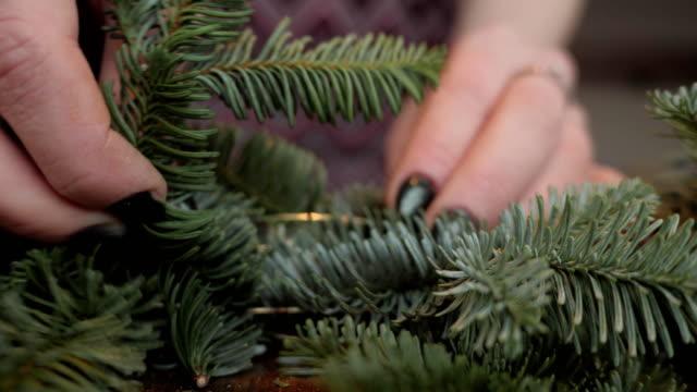 Hand closeup. Florist at work: woman hands making christmas decorations garland of fir Nobilis. Happy new year dinner feast video