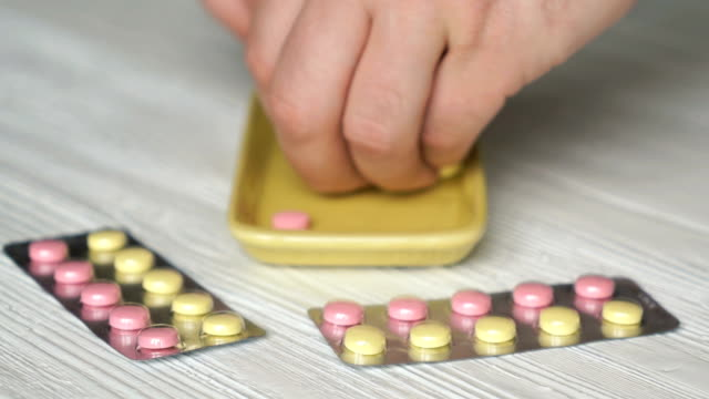 Hand collects the tablets in a yellow container video