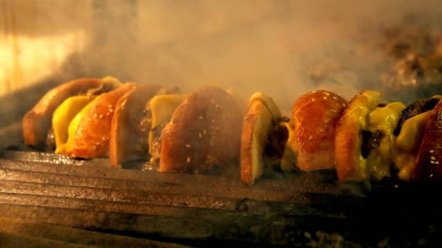 stockvideo's en b-roll-footage met hand koken hamburgers op een hete vlammende grill - foodtruck