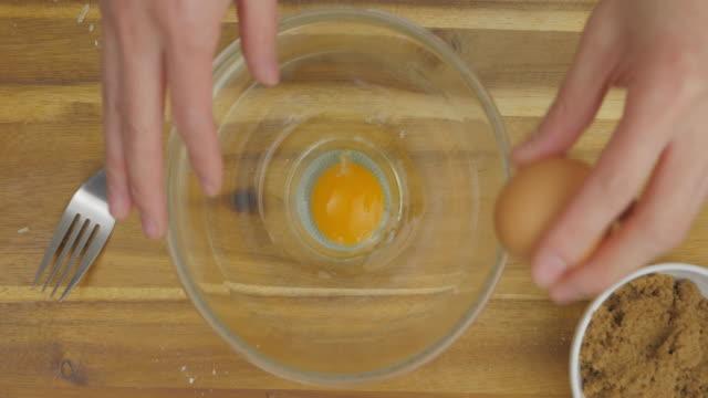 stockvideo's en b-roll-footage met hand spleet eieren in een kom mengen - ei