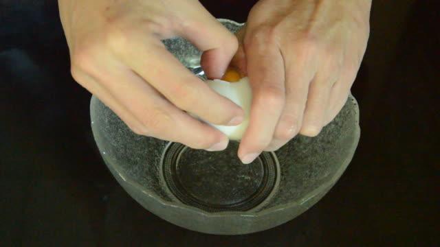 hand cracked white eggshell in glass bowl video