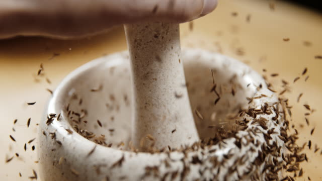 SLO MO Hand cracking cumin seeds in the mortar Super slow motion shot of an unrecognizable person cracking cumin seeds in the mortar. spice stock videos & royalty-free footage